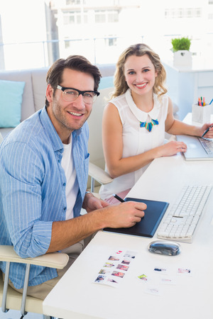 graphics tablet: Casual photo editors using graphics tablet in office Stock Photo
