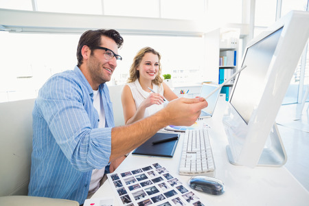 editors: Photo editors working together on graphics tablet in office Stock Photo