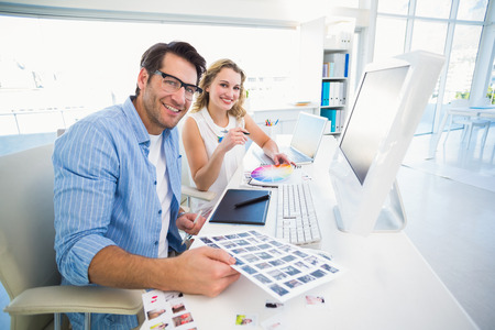 editors: Two happy photo editors working with contact sheets in office