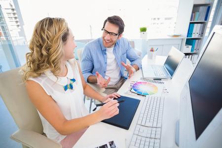 digitizer: Smiling photo editors using digitizer in office