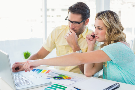 designer at work: Creative design team during brainstorming working on laptop in office Stock Photo