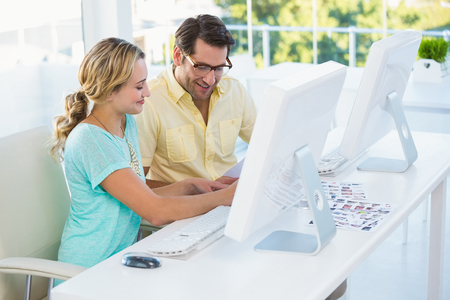 editors: Photo editors choosing photos on computer screen in office Stock Photo