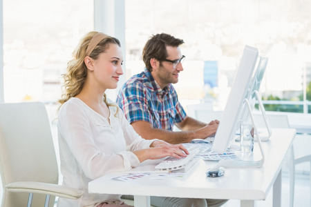 editors: Thoughtful photo editors looking at their screens in their office Stock Photo