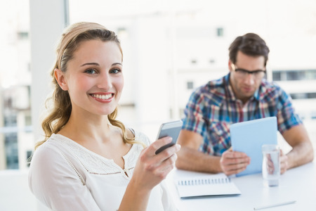 Woman sending a text message with her colleague behind in office
