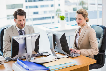Focused business people using computer in office
