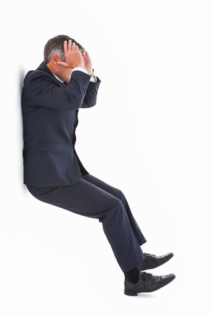 Stressed businessman with head in hands on white background photo