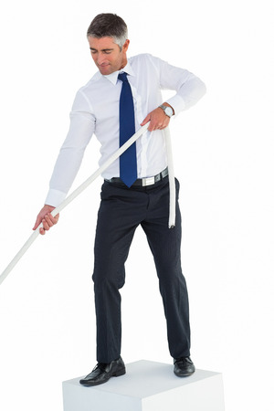 Businessman standing on cube pulling rope on white background