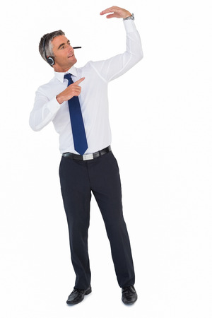 Smiling businessman with headphone pointing on white background photo