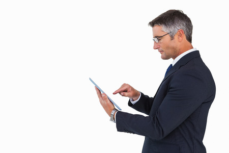 cut wrist: Businessman in glasses using his tablet pc on white background