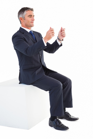 arms out: Businessman sitting on a cube with arms out on white background