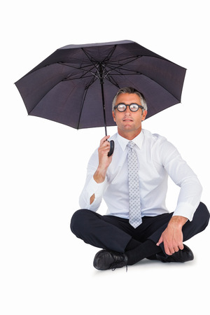 sheltering: Businessman wearing glasses sheltering with umbrella on white background