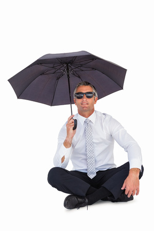 sheltering: Businessman wearing sunglasses and sheltering with umbrella on white background