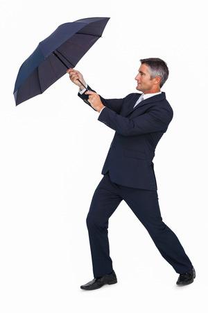 sheltering: Businessman pushing the wind with umbrella on white background