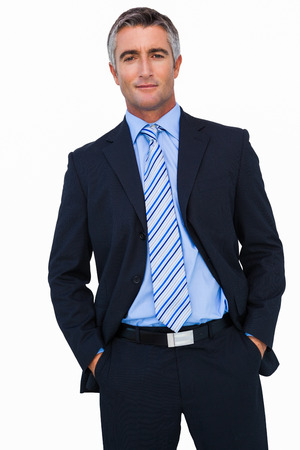 out of business: Smiling businessman in suit with hands in pocket posing on white background