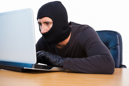 thievery: Burglar with balaclava hacking a laptop on white background Stock Photo