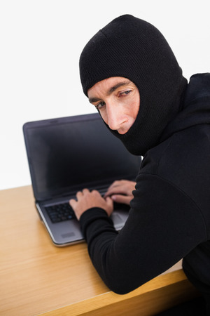 thievery: Burglar hacking a laptop and looking behind him on white background Stock Photo