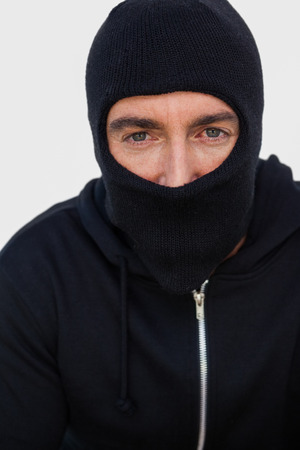thievery: Portrait of a burglar with black jacket and balaclava on white background