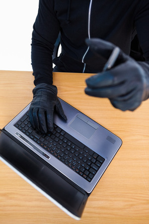 intruding: Mid section of a burglar using laptop and smartphone on white background Stock Photo