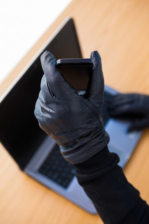 thievery: Hands with leather gloves using laptop and smartphone on white background