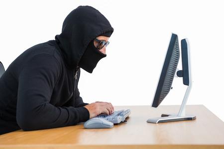 intruding: Burglar with sunglasses typing on keyboard on white background Stock Photo