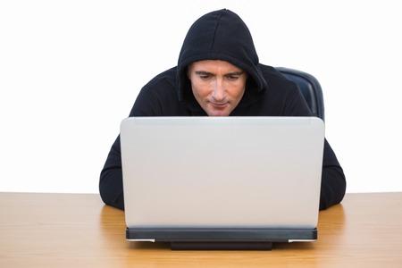 intruding: Burglar in hood jacket using laptop on white bakcgorund Stock Photo
