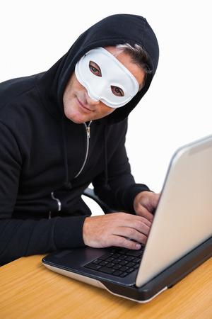 intruding: Hacker with white mask using laptop and looking at camera on white background