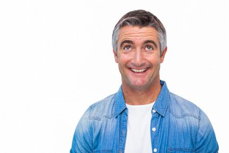 ropa casual: Hombre alegre en ropa casual mirando hacia arriba sobre fondo blanco