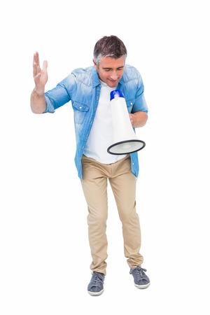 ropa casual: Hombre en ropa casual hablando en meg�fono en blanco bakcground Foto de archivo