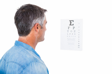 grey hair: Man with grey hair doing a eye test on white background