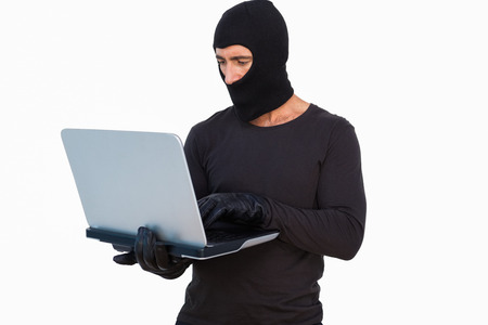 thievery: Burglar with leather gloves using laptop on white background