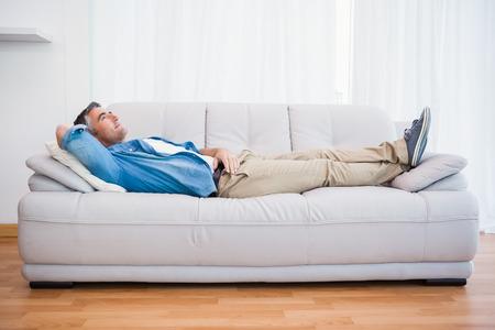 Lachende man liggen en ontspannen op de bank thuis in de woonkamer Stockfoto