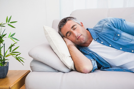sleeping at desk: Man with grey hair sleeping on the couch at home in the living room Stock Photo