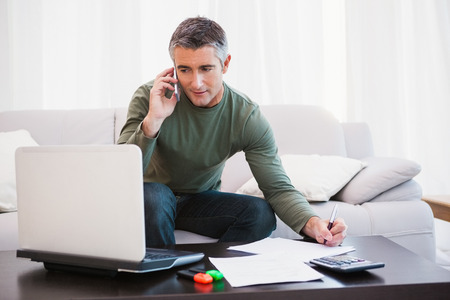 phone call: Man with laptop phoning and taking notes at home in the living room Stock Photo