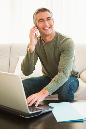phone call: Happy man on the phone using laptop at home in the living room