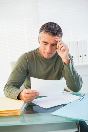paper work: Smiling man with grey hair reading paper in his office