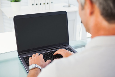 grey hair: Man with grey hair typing on laptop in his office 스톡 사진