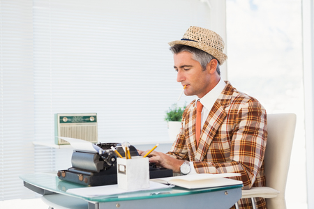 unfashionable: Retro man in straw hat typing on typewriter in his office Stock Photo