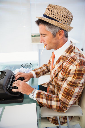 unfashionable: Vintage man in straw hat typing on typewriter in his office