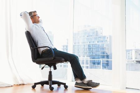 Homem de sorriso com os vidros que sentam-se na cadeira do escrit