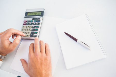 person writing: Hand of man using a calculator at desk in the office Stock Photo
