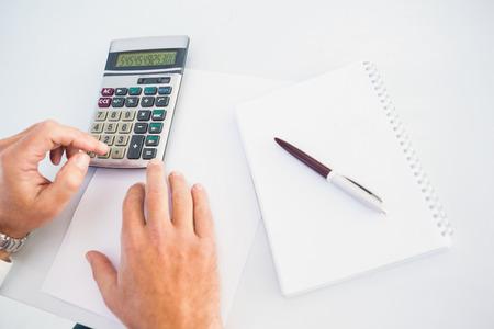 persona escribiendo: Mano del hombre usando una calculadora en el escritorio en la oficina