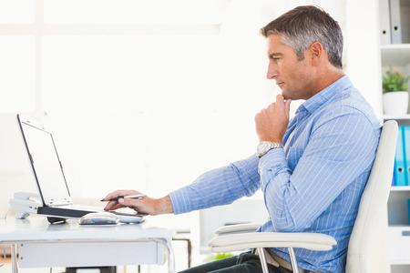 노트북을 사용하고 그의 사무실에서 생각하는 셔츠에있는 남자