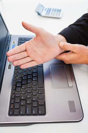 carpel: Hand of man touching his wrist in the office