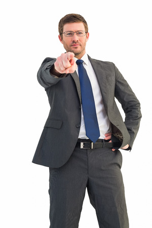 frowning: Frowning businessman pointing at camera on white background