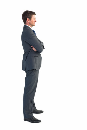 Businessman standing with arms crossed on white background