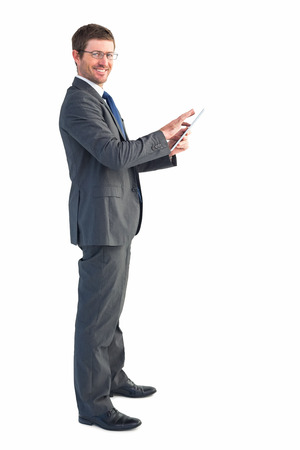 Businessman using his tablet pc on white background photo