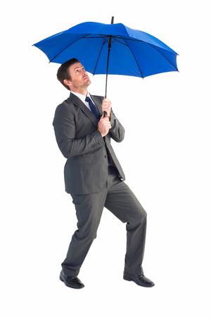 sheltering: Businessman sheltering under blue umbrellaon white background