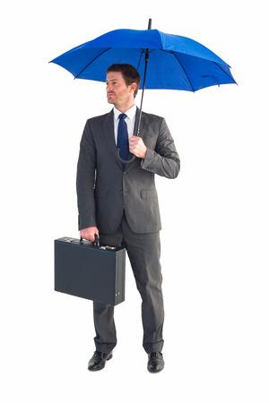 sheltering: Businessman sheltering under blue umbrella on white background Stock Photo