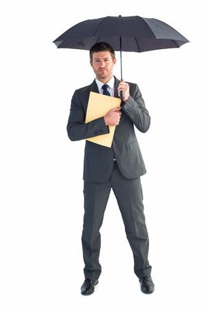 sheltering: Businessman sheltering under umbrella holding file on white background
