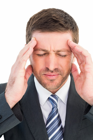 pounding head: Businessman getting a headache on white background